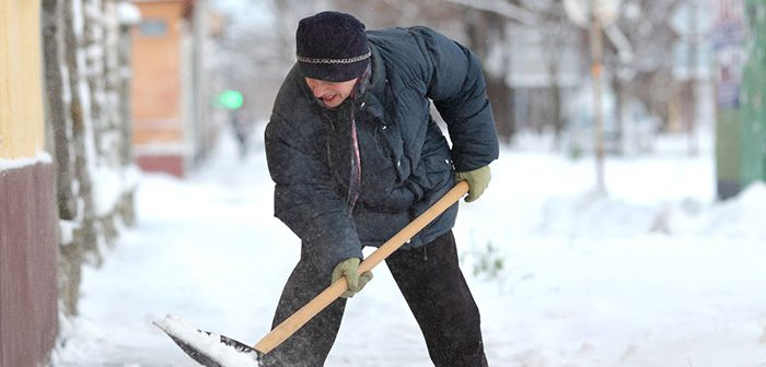 Man snow shoveling sidewalks.