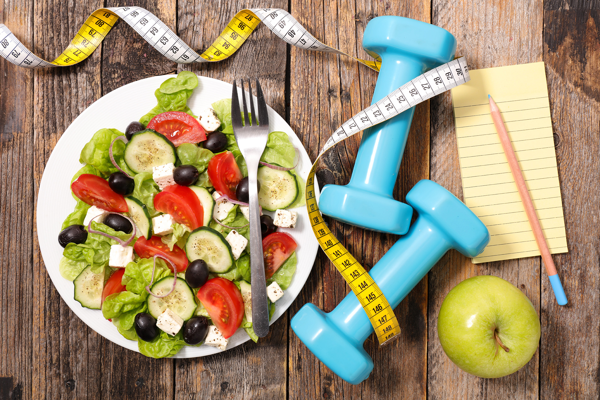 plate of salad, tape measure, green apple and light blue weights.