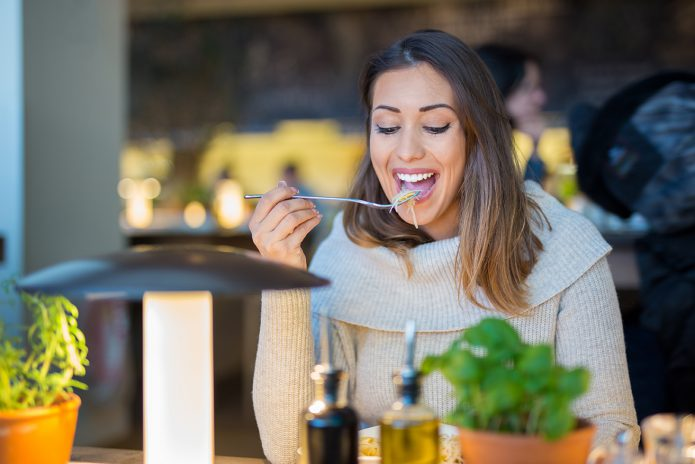 Beautiful woman eating lunch at a restaurant while smiling and looking at the food