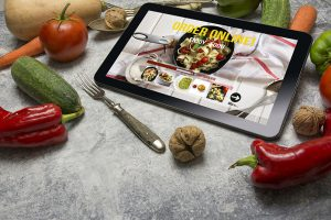 Tablet with Online food Delivery app on screen. Healthy food concept