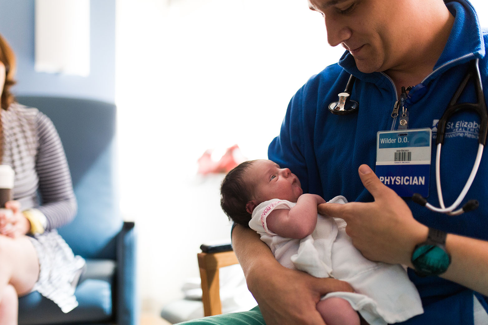 Male doctor holding newborn baby