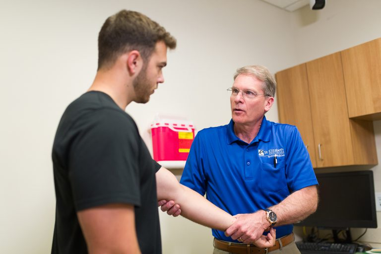 Dr. Miller examines male athlete's arm