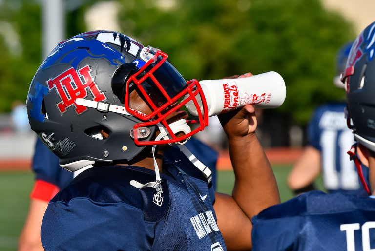 Football player drinking water on hot summer day