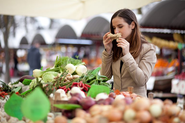 Brown haired female smelling ginger root at farmers market in front of colorful vegetable stand.