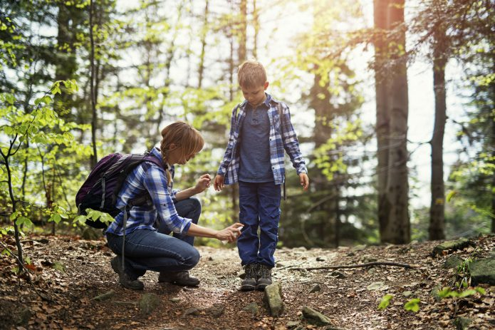 Mother sprays son with insect repellent in the woods