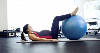 Pregnant woman with exercise ball doing pilates