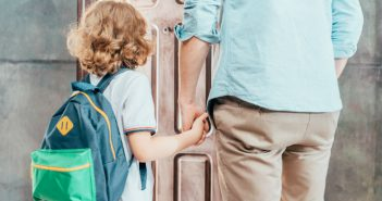 Child wearing backpack holding parent's hand
