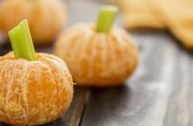 Peeled oranges with celery stuck in top for a pumpkin look