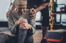 Woman stretching knee with trainer