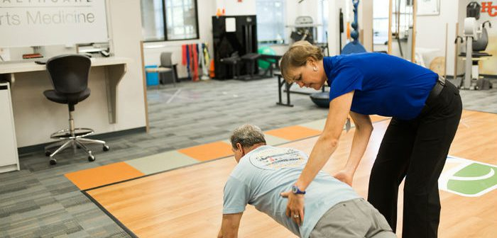 Physical therapist helping patient do plank exercise
