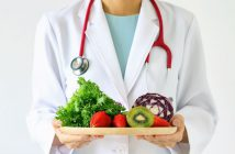 Dietitian in white lab coat with red stethoscope around neck holding plate of fresh fruits and vegetables