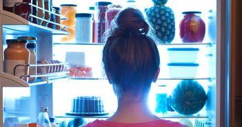 Woman with hair up standing in front of open fridge late at night.