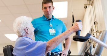 Physical Therapist helps older female patient exercise