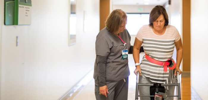 Physical Therapist helps patient walk down hallway after joint replacement