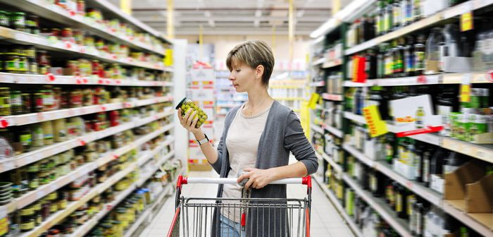 Caucasian lady reading label of canned goods at grocery store.