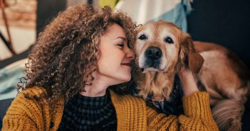 Woman with curly hair hugging old golden retriever