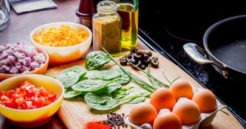 Countertop with bowls of eggs, cheese, seasonings, oil, spinach, black olives, tomatoes, onions.