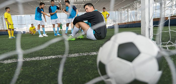 Hispanic soccer player sitting on indoor soccer field with soccer ball in foreground