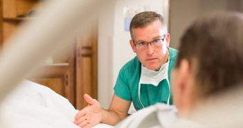 Male surgeon consulting with male patient at bedside.