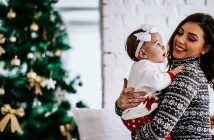 Mom holding newborn baby girl in front of Christmas tree.