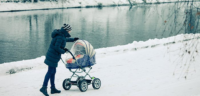 Woman pushing baby stroller next to a pond in the snow.