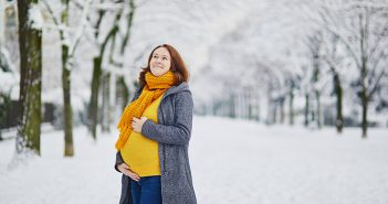 Pregnant woman standing outside in snow