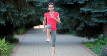 Woman runner doing warm-up and cool-down exercises outdoors.
