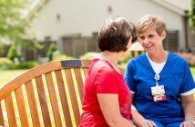 Palliative Care nurse speaks with female patient outside on park bench.