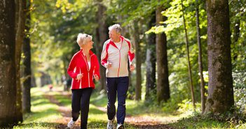 Older couple power walking in the words