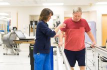 Female physical therapist helps male stroke patient walk.