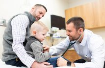 Dr. Philip Hartman working with young boy and his father in doctor's office exam room.