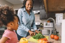 African American mother and daughter cutting vegetables together in kitchen.