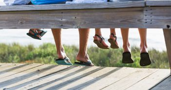 Family sitting on bench at the beach wearing flip flops.