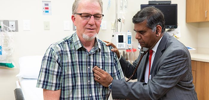 Dr. DP Suresh examines older male patient.