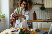African American woman cooking with fresh vegetables in bright kitchen