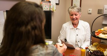 Dietitian speaking to patient about healthy options at a desk in an office.