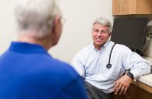 Dr. Jeffrey Reichard meeting with male patient.