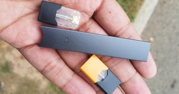 Male holding piece of JUUL, similar look to USB drive.