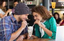Happy couple looking at each other while having milkshake in restaurant