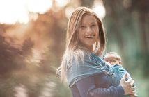 lifestyle shot of young woman walking with her baby girl in the nature.