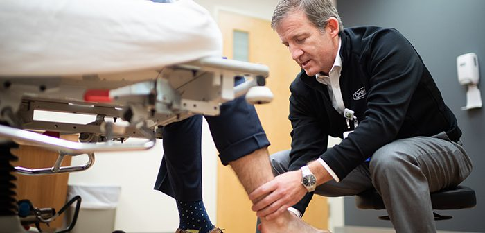 Dr. Gates looking at a patient's ankle.