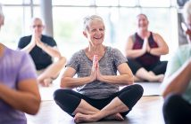 A group of seniors are sitting crosslegged and meditating in a fitness center. 1053396360 Example of service planned to be available in the doTERRA Center for Integrative Oncology