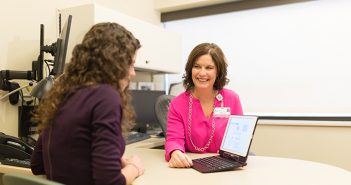 Genetic counselor showing a patient options on a laptop.