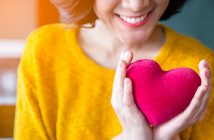 close up of woman hands in yellow sweater holding pink heart. people, age, family, love, valentine and health care concept