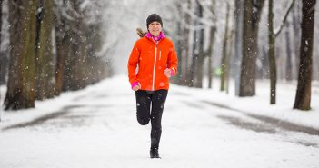 Women running in snow with proper weather protective gear.