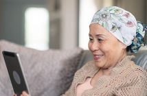 A senior adult woman of Chinese descent has cancer. The happy woman is using a digital tablet to video message friends and family. She is spending time at home. The woman is smiling at the screen. She is wearing a bandana to hide her hair loss from chemotherapy treatment.