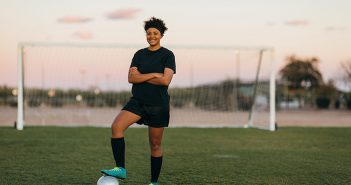 A female high school soccer player in practice uniform poses for a portrait while on the pitch in Arizona, USA. She is a young woman athlete who loves to compete in the sport of soccer.