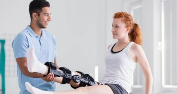 Young woman wearing a brace during rehabilitation with her physiotherapist