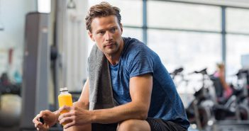 Handsome young man in sportswear holding bottle of fresh orange juice while resting at gym.Thoughtful fit man sitting alone holding a bottle of energy drink. Guy take break after fitness exercise on bench.