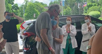 Scott Bona, COVID-19 patient leaving hospital for first time, hugging family.